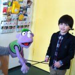 Foto: Junge hält die Führungsstäbe eine Handpuppe auf einem Arm. Blick zum Betrachter.