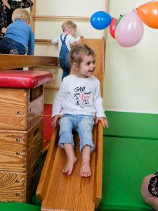 Foto: Mädchen rutscht lachend auf einer Holzrutsche