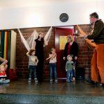 Foto: älterer Mann mit oranger Hose und Gitarre sinbft mit Kindern und deren Eltern auf der Bühne.