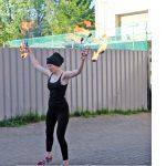 Foto: Frau steht mit brennenden Feuerreifen in beiden hochgesteckten Händen auf geplastertem Boden. Wellblechwand im Hintergrund.