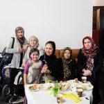 Foto: Gruppe von Frauen mit Kopftüchern und Kind mittendrin sitzen hinter einem Tisch mit Gebäck auf einer Couch und lächeln.