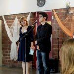 Foto: Die Leiterin Sibylle Büchele im Hinmtergrund mit der Stadträtin Frau Dr. Obermeyer auf der Bühne vor einem Mikrofon.