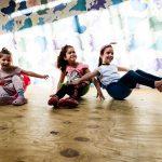 Foto: 3 Mädchen balancieren sitzend jeweils in einer halbrunden Plastikwanne