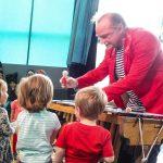 Foto: älterer Herr mit rotem Jacket steht hinter einem Xylophon und reicht den davor stehenden Kinder einen Rasierpinsel.