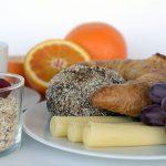 Foto: Frühstück mit Müslischale, Teller mit Käse, Obst und Backwaren sowie Orangen und Tasse Kaffe im Hintergrund.
