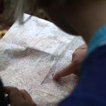Foto: Blick von hinten über die Schulter. Ein Finger zeigt auf eine Landkarte.