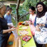 Foto: Frau mit Kopftuch und ohne und 2 Mädchen belegen Pizzateig na einem langen Tisch.