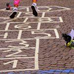 Foto: Kinderfüßen springen über Speil auf Straße