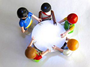 Foto: 5 Playmobilfiguren stehen um einen Tisch. Blick von oben.