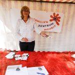 Foto: Frau im Stand hinter Teich mit rote Tischdecke reicht ein Faltblatt. Logo FZM im Hintergrund.