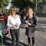 Foto: zwei Frauen stehen nebeneinander während des Straßenfestes auf der Straße und halten Faltblätter in den Händen. Blick zum Betrachter.