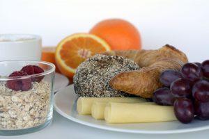 Foto: Frühstück mit Hörnchen, Brötschen und Weintrauben auf Teller, Müslischüssel mit Himbeeren und Orangen im Hintergrund
