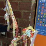 Foto: Kinderhände halten slebsgebaute Fahnen aus bunten Plastikstreifen an Holzstäben