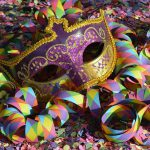 bunte Maske und bunte Papierschlangen auf buntem Konfetti