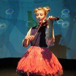 Foto: Frau mit rotem Rock spielt Violine auf einer Bühne mit blauem Hintergrund