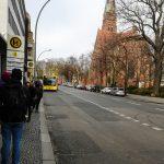 Foto: Blick von einer Bushaltestelle mit Haltestellen Schild und wartenden Reisenden. Buss rollt in der Ferne an.
