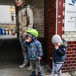 Foto: 2 Kinder stehen mit ihrem Vater wartend in einer Tordurchfahrt