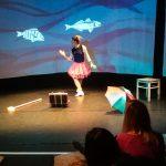 Foto: Blick auf die Bühne - tanzende Frau vor Leinwand mit 2 Fischen