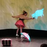 Foto: Blick auf die Bühne - Tänzerin hält einer Schafabbildung auf der Leinwand etwas zu fressen hin