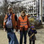 Foto: 2 Erwachsene in Warnwesten mit Müllbeutel und ein Kind stehen nebeneinander mit Blick zum Betrachter