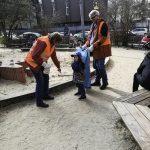Foto: 2 Erwachsene in Warnwesten mit Müllbeutel und ein Kind beim Müll sammeln auf einem Spielplatz