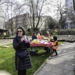 Foto: beim Pausieren - Erwachsene und Kinder am Esstisch im Hintergrund, eine Frau mit Essschüssel in der Hand im Vordergrund