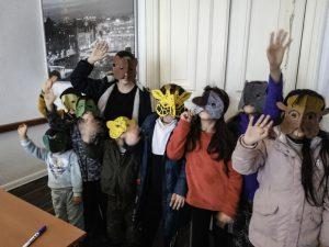 Foto: viele Kinder stehen mit gebastelten Masken im Gesicht winkend im Raum vor einer großen Tür