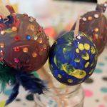 Foto: drei bemalte Ostereier mit Federn und Edelsteinen beklebt auf Holzstäben in einem Glas stehend