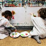 Foto: zwei Kinder malen an einer Wand, auf der ein Blatt Papier aufgespannt ist