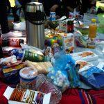 Foto: Eine Picknickdecke auf der Tee. Cola,Saft und viele Süßigkeiten liegen