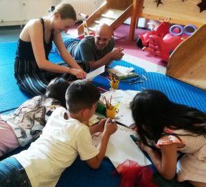 Foto: zwei Erwachsene und drei Kinder malen auf dem Boden liegend und sitzend