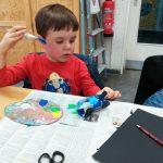 Foto: Kind an Tisch sitzend hält blauen Pinsel in der rechten Hand und malt Klopapierrolle an