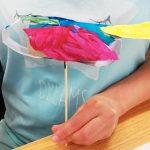 Foto: Kinderhand hält einen aus Klopapierrollen, bunten, gebastelten Vogel