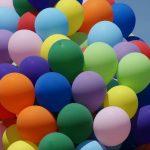 Foto: eine große Traube bestehend aus vielen bunte Luftballons vor blauem Himmel