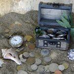 Foto: oben rechts eine kleine Schatztruhe auf Sand stehend, davor Münzen, Muscheln und eine Uhr im Hintergrund eine Schatzkarte