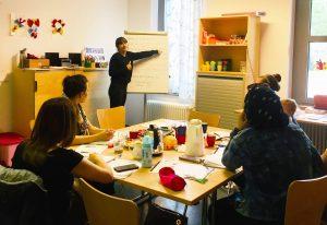 Foto: Raum mit Tisch in der Mitte an dem fünf Frauen sitzen während eine sechste Frau an einem Whiteboard etwas zeigt