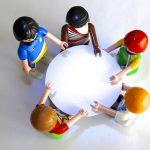 Foto: Tisch von oben, an dem fünf Playmobilmännchen sitzen