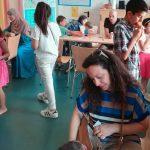 Foto: Raum mit Tisch und Stühlen um und an dem Erwachsene und Kinder sitzen und stehen