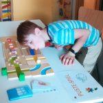 Foto: Ein Tisch mit einem Spiel drauf, rechts im Bild ein Junge, der auf das Spiel pustet