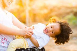 Foto: Kind auf Schoß einer älteren Person, diese hält Kind fest, dass sich zurück lehnt und lacht