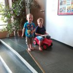 Foto: zwei Kinder auf einer Rampe, das rechte Kind sitzt auf einem Bobby Car