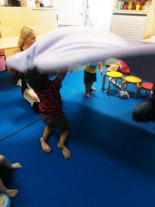 Foto: vier Personen, zwei davon Kinder, schwingen eine Decke nach oben