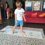 Foto: Eine bunte Decke liegt auf dem Boden, darauf ein Blatt mit aufgemalten Fußabdrücken, auf dem ein Junge steht.