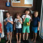 Foto: fünf Kinder stehen vor einer dunklen Backsteinwand und halten Stäbe mit gebastelten Figuren