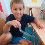 Foto: Ein Junge sitzt auf einem Stuhl und hält eine silberne, gebastelte Schlage in der rechten Hand