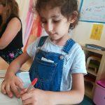 Foto: Mädchen sitzt am Tisch und malt mit einem rotem Stift auf silbernen Karton