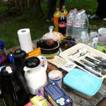 Foto: Ein Tisch draußen, gedeckt mit Teekannen, Tee, Tupperwahre, Besteck und Tassen