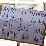 Foto: Pappschild auf dem in blauer Kindersschrift Auto Fabriken machten jetzt zu denn dann rufe ich ja!!!! steht