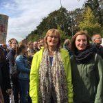 Foto: Menschenansammlung davor zwei Frauen, links mit gelber, rechts mit grüner Jacke