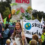 Foto: Frau in Menschenmenge hält Schild mit Fisch und aufgeklebten Plastik worauf Findet Nemo steht
